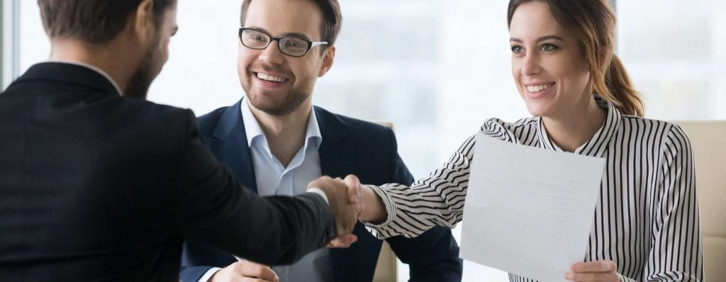 Bilde av to personer som inngår en avtale i et møte