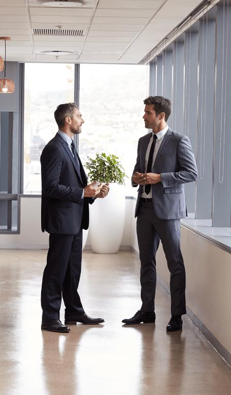 Bilde av to menn som prater sammen i et kontorlandskap