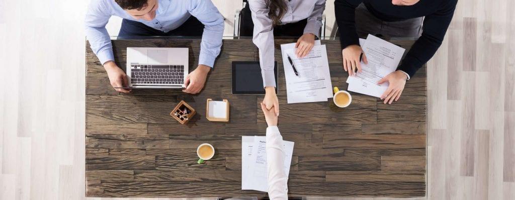 Bilde ovenfra av mennesker som inngår en avtale i et møte