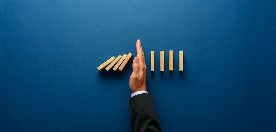 Bilde av hånd som stopper dominoeffekten